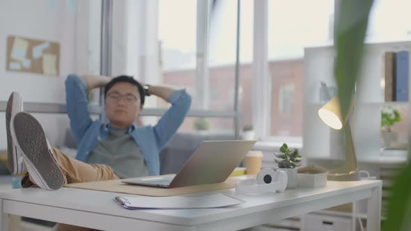 Asian Office Worker Resting With Legs