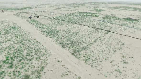 Flying over Dunes over farming in the Desert and showing