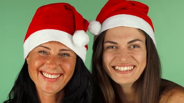 2607d78a2 Happy Women in Santa Claus Hats Laughing Joyfully To the Camera by ...