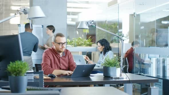 Busy International Corporate Office Caucasian Man Working At His Desk On A Laptop Stock Footage