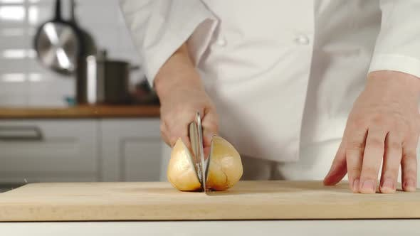Chef Chopping A Head Of Onion On Wooden Board While Cooking