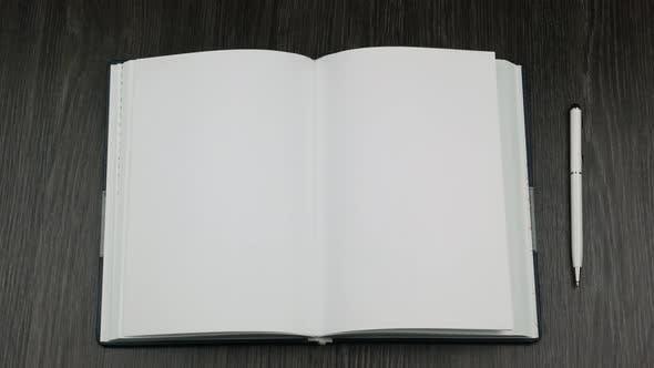Blank open book on dark wooden desk  Businessman flips the Page  by