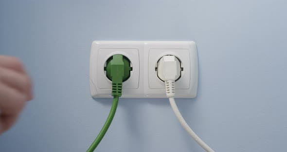 Hand Plugging Green Power Cord In Socket Concept Eco Green