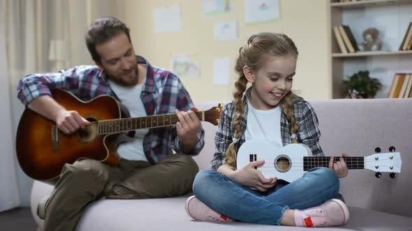 Dad With Guitar and Daughter With Ukulele Playing Song