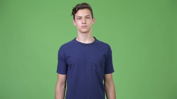 Young Handsome Teenage Boy With Arms Crossed By