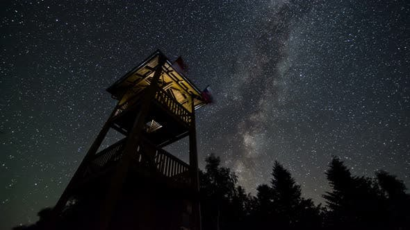 Milky Way Galaxy and Stars over Lookout Tower in Starry Night Sky in