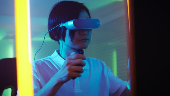8e764d4c903 East Asian Pro Gamer Puts On Virtual Reality Headset Plays Online Video  Game with Joysticks (Stock Footage)
