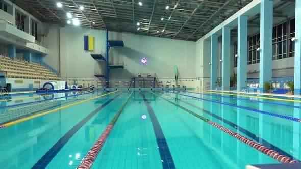 Turning Off Lights in Empty Pool with Clear Water and Dividers Track for  Swimming. Blue Water in