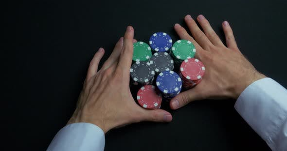 Stack Of Poker Chips And Two Hands On Table by