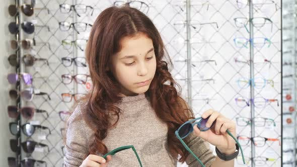 2074359eb5 Pretty Little Girl Looking Confused Choosing Between Two Pairs of Sunglasses  1080p (Stock Footage)