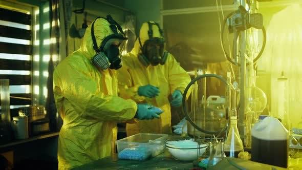 In the Underground Laboratory Two Clandestine Chemists Wearing