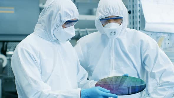 Two Scientists/ Technicians in Sterile Suits Check