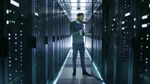 IT Technician Works on Laptop in Big Data Center full of