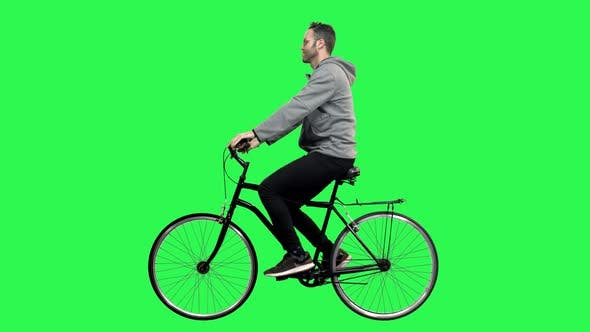 Happy Man Riding a Bicycle Over a Green Screen, Looking