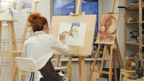 Woman Artist Painting Watercolor Picture In Her Studio By